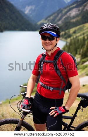 Biker beside a beautiful mountain lake - stock photo