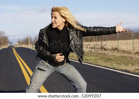 Biker chick playing air guitar in the road - stock photo