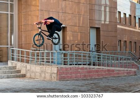 Biker doing high rail hop trick on bmx, front view - stock photo