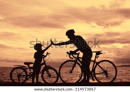 Biker family silhouette , daddy and son at the beach at sunset. - stock photo