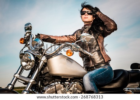 Biker girl in a leather jacket on a motorcycle looking at the sunset. - stock photo