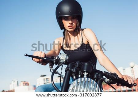 Biker girl in helmet sitting on vintage custom motorcycle. Outdoor lifestyle portrait - stock photo