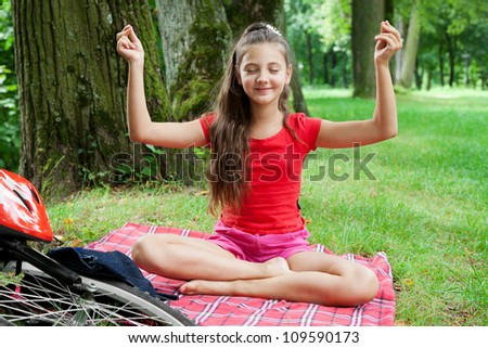biker girl relaxing in yoga pose on grass in a park - stock photo