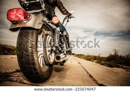 Biker girl riding on a motorcycle. Bottom view of the legs in leather boots. Focus on the rear wheel. - stock photo
