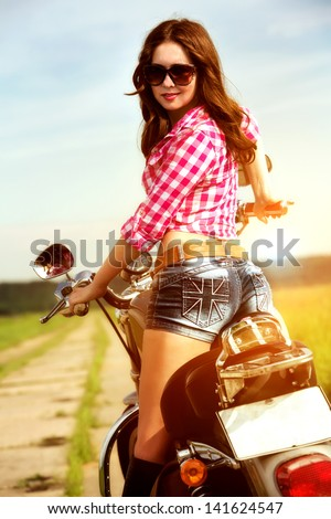 Biker girl with sunglasses sitting on motorcycle - stock photo