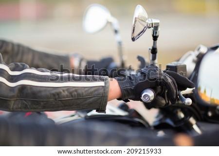 Biker hand rests on the steering wheel motorcycle - stock photo