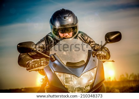 Biker in helmet and leather jacket racing on the road with the sun in the background - stock photo