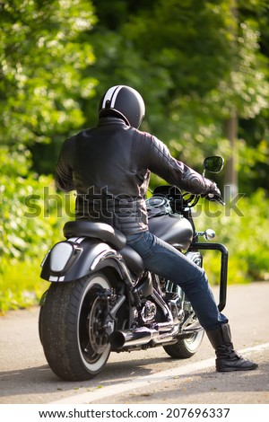 biker in mask sitting unknown on big chopper bike on road - stock photo