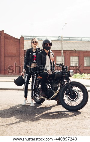 Biker man and girl sits on a vintage custom motorcycle in city. Outdoor lifestyle portrait - stock photo