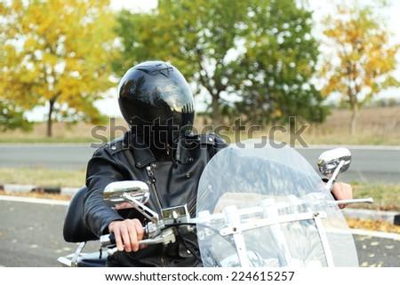 Biker man in black helmet sits on bike - stock photo