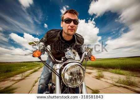Biker man wearing a leather jacket and sunglasses sitting on his motorcycle and racing on the road. - stock photo