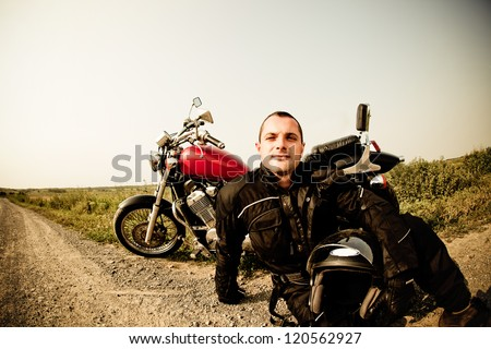 Biker on the country road against the sky - stock photo