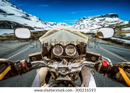 Biker rides a motorcycle on a slippery road through a mountain pass in Norway. Around the fog and snow. First-person view. - stock photo