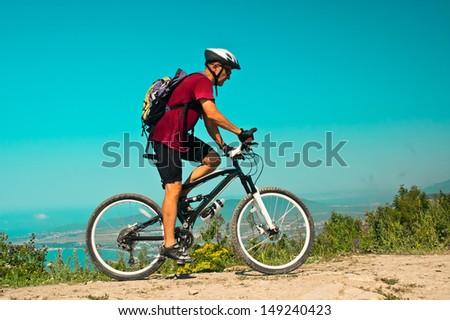 Biker rides at mountain - stock photo