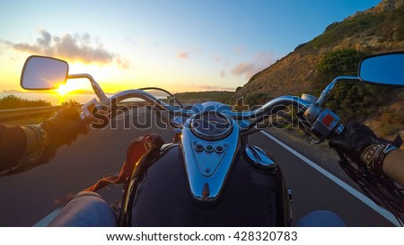 biker riding a classic motorcycle at sunset - stock photo
