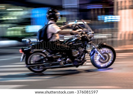 Biker riding a motorbike in the city at night, motion blurred. - stock photo