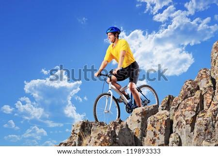 Biker riding a mountain bike on rocks - stock photo