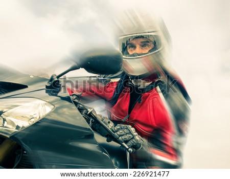 biker riding fast on his sport motorbike. speed blur effect - stock photo