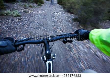 Biker's hands at handlebar while riding mtb bike - stock photo