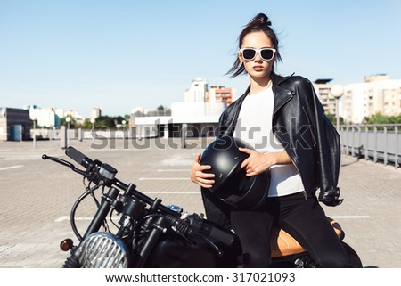 Biker sexy woman sitting on vintage custom motorcycle. Outdoor lifestyle portrait - stock photo