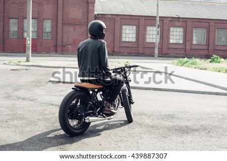 Biker sitting on vintage custom motorcycle. Outdoor lifestyle portrait - stock photo