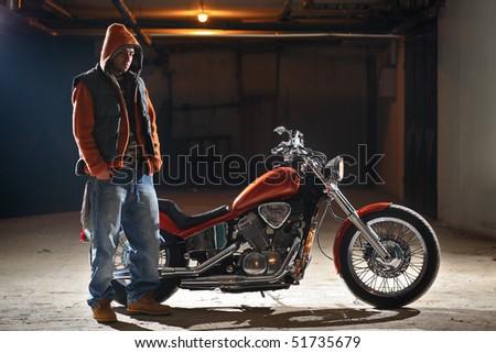 Biker standing next to a bike - stock photo