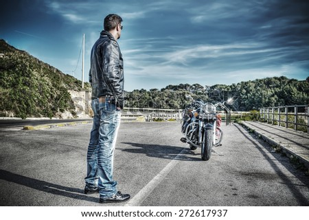 biker standing next to a classic motorcycle in hdr tone mapping effect - stock photo