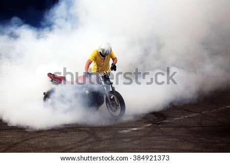 biker staying on bike on road with smoke of the tire, burn out in the moto show - stock photo