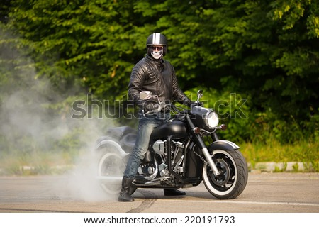 biker staying with unknown big chopper bike on road with smoke of the tire - stock photo