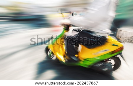biker with a motorcycle in motion blur on city road in sunny day - stock photo