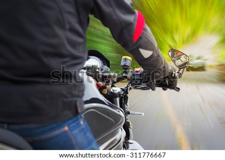 Bikers driving a motorcycle on asphalt road  - stock photo