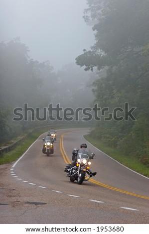Bikers in a fog - stock photo