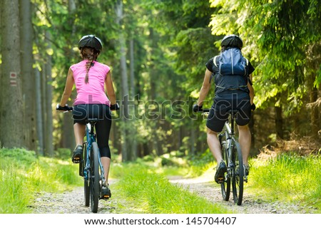 Bikers in forest cycling on track from behind - stock photo
