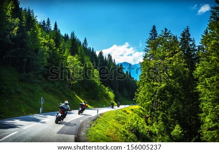Bikers in mountainous tour, traveling across Europe, curve highway in mountains, scene destinations, extreme transport, active lifestyle - stock photo