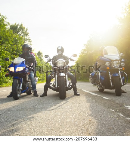 bikers sitting on their bikes, big chopper bike, sport bike on road - stock photo