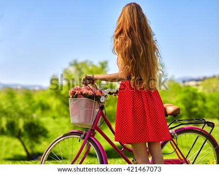 Bikes bicycle girl. Girl with long blond hair wearing red polka dots dress looking into distance keeps bicycle with flowers basket.  Green grass. Back view. - stock photo