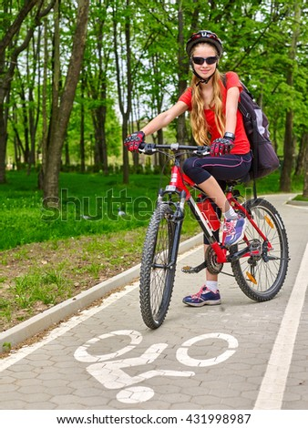 Bikes bicyclist girl. Girl wearing bicycle helmet and glass with rucksack ciclyng road bicycle. Girl rides on bike lane with road sign. There is sidewalk at background. Front view. - stock photo