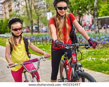Bikes bicyclist girl. Girls wearing bicycle helmet with rucksack ciclyng bicycle. Girls children cycling on yellow bike lane. Bike share program save money and time. - stock photo