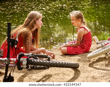Bikes cycling family. Happy mother and daughter rides bicycle. Family have rest near water in park. Bicycles are on coast. - stock photo