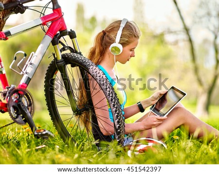 Bikes cycling girl. Girl rides bicycle. Girl wearing headset watch in pc tablet and listing music near bicycle. Cycling on bicycle is good for health. Cyclist looking pc tablet. - stock photo