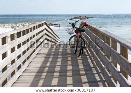 Bikes on a boardwalk leading to the beach on the Alabama/Florida gulf coast. - stock photo