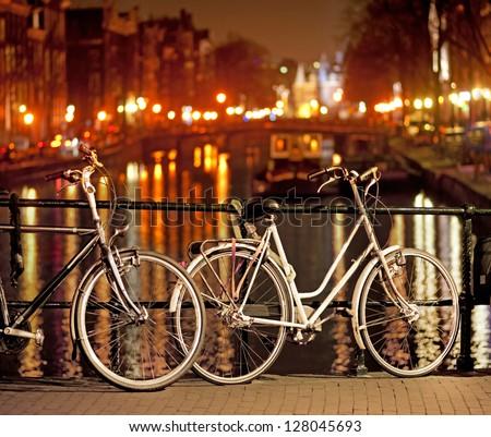 Bikes parked on bridge in Amsterdam at night - stock photo