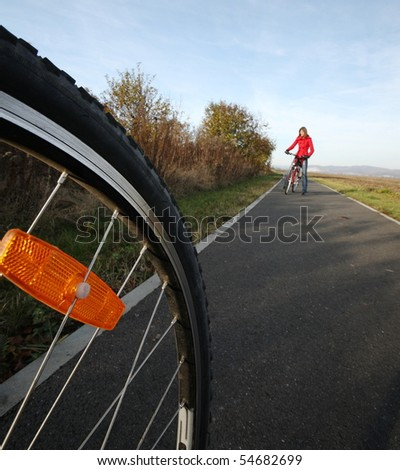 Biking (the image is motion blurred to convey movement; focus is on the wheel, the female biker is left out of focus) - stock photo