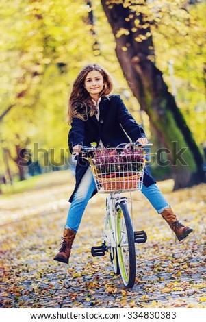 Biking, Young and beautiful girl on bike in autumn park - stock photo