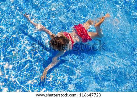 bikini kid girl swimming on blue tiles pool in summer vacation - stock photo