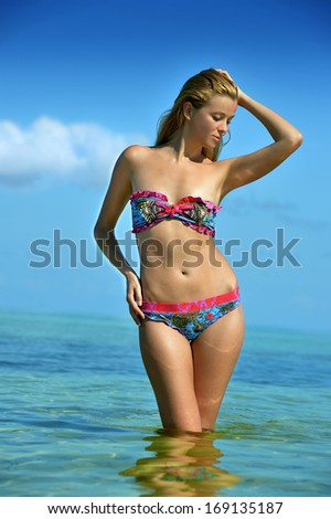 Bikini model posing sexy in front of camera at tropical beach location standing at the water - stock photo