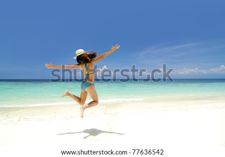 Bikini young girl is jumping up in the air at the beach - stock photo