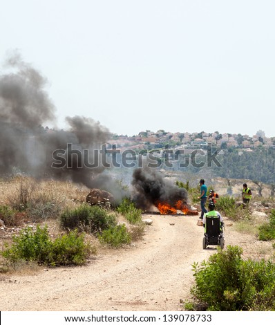BIL'IN, PALESTINE - MAY 17: People walking by tires burning on the road leading to the wall of separation, on a protest against the Israeli occupation of Palestine on May 17, 2013 in Bil'in, Palestine - stock photo