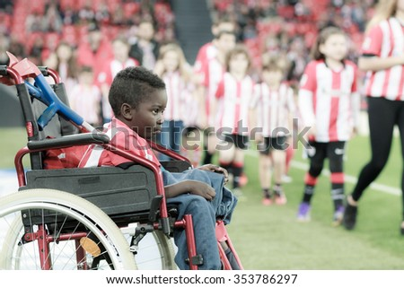 BILBAO - DECEMBER, 20: A boy in a wheelchair  waiting to take the photo with the players before the Spanish League match against Levante UD at San Mames Stadium on December 20 2015 in Bilbao Spain - stock photo