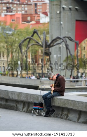 BILBAO, SPAIN - APRIL 4, 2014: A man prepares his tenor sax to play on one of the walks in the city of Bilbao, near the river Nervion. - stock photo